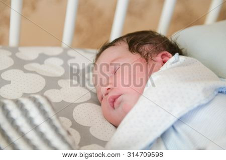 The Baby Sleeps In The Crib. Charming Girl Sleeps In A Bed For Sleep, Attached To The Bed Of Parents