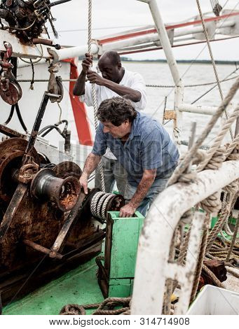 BEAUFORT, SOUTH CAROLINA-SEPTEMBER 14, 2015: Two commercial fishermen work on equipment on the deck of a ship off the coast of South Carolina.