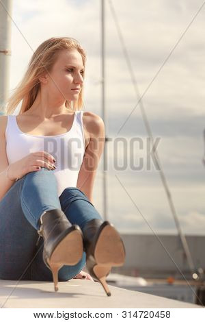 Resting And Relaxation. Young Beauty Woman Relaxing On Marina On Fresh Air. Fashionable Blondie Girl