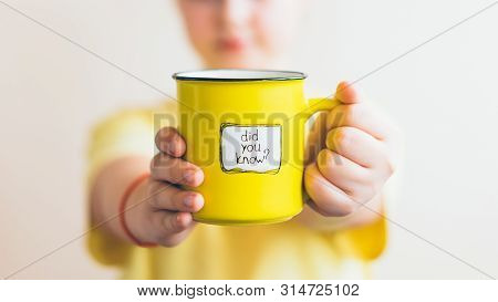 A Girl With A Yellow Cup In Her Hand, On Which Was Written Did You Know