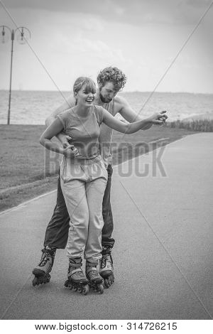 Love Romance Sport Fitness Leisure Concept. Teen Couple Together On Skates. Girl And Boy Riding Roll