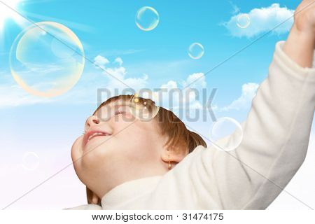 The Small Girl Plays With Soap Bubbles