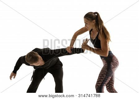 Man In Black Outfit And Athletic Caucasian Woman Fighting On White Studio Background. Womens Self-de