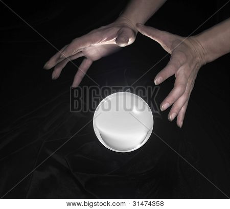 high angle shot of a glowing crystal ball surrounded by black crinkly fabrics and two hands around poster