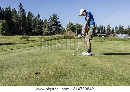Boy Makes Contact On The Ball With The Putter.