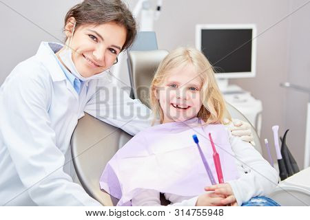 Friendly dentist or medical assistant with child as a patient and toothbrushes for dental health