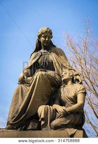 An Angel Comforting A Grieving Women Depicted In Stone
