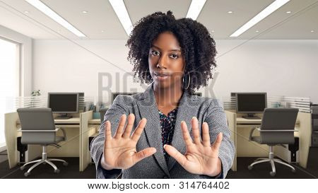 Black African American Businesswoman In An Office With A Stop Gesture.  She Is An Owner Or An Execut