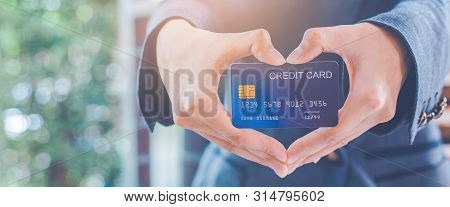 Woman Hand Are Holding A Credit Card And Making A Heart-shaped Hand.