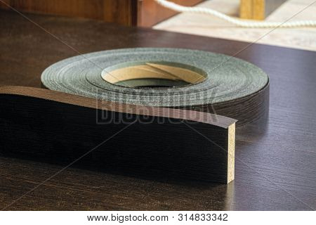 Roll melamine edge for finishing of furniture on laminated chipboard sheets wenge color. Limited depth of field. poster