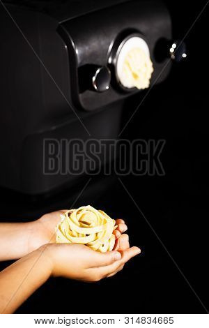 Hands Of A Little Girl Holding E Fresh Home-maded Tagliatelle Pasta. Pastamaker In Background