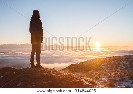 View From The Back. A Lonely Standing Man High In The Mountains Looks At The Setting Sun And The Sun