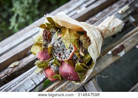 Bunch of rotten fruit and wilted flowers lay on old wooden boards poster