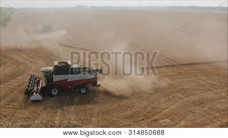 A New Combine In A Field. Combines Harvested Wheat From The Fields. An Agricultural Combine Harvests
