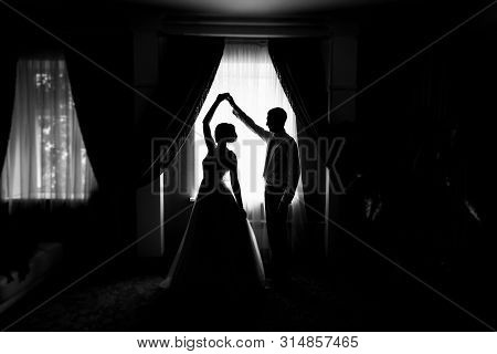 Silhouette Of Bride And Groom By The Window. Bride And Groom Dancing. Newly Married Couple. Wedding