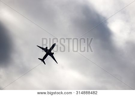 Airplane Silhouette On Storm Sky Background. Commercial Plane Taking Off Among Dark Clouds, Turbulen