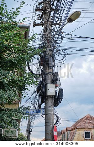 Street Pole With Tv, Internet, Telephony, And Electricity Cables Hanging From It In An Unorganized M