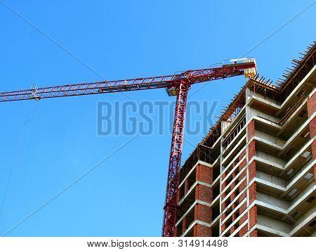 Concrete Red Brick Building Under Construction. Construction Site. Crane Near Building Against The B