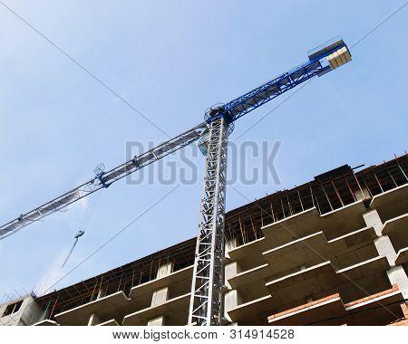 Concrete Building Under Construction. Construction Site. Crane Near Building.