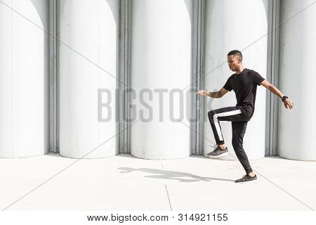 Athletic young afroamerican man running on the promenade. Black Male runner sprinting outdoors. Healthy lifestyle concept. poster