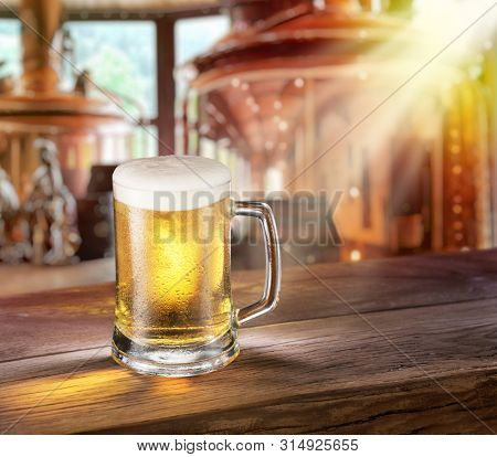 Beer mug on wooden table and copper brewing cask at the background. Craft brewery.