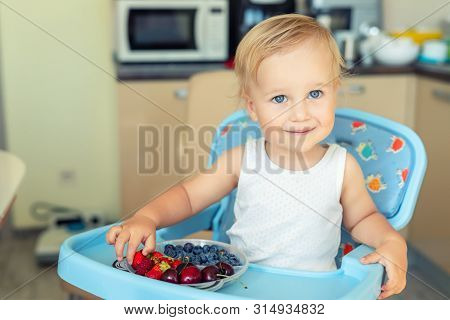 Adorable Cute Caucasian Blond Toddler Boy Enjoy Tasting Different Seasonal Fresh Ripe Organic Berrie