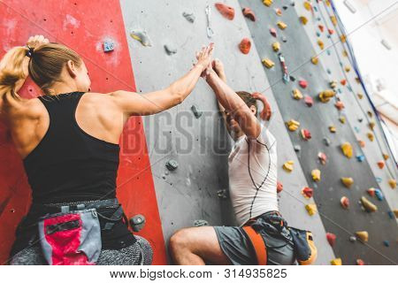 Couple Of Athletes Climber Moving Up On Steep Rock, Climbing On Artificial Wall Indoors. Extreme Spo