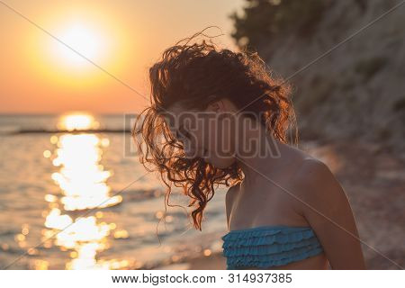 Close-up Portrait Of A Beautiful Girl At Sunset. Long, Brunette Curly Hair. Beauty Care