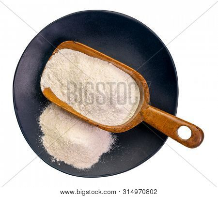 Cassava (yuca) flour on a wooden scoop and plate. It is a gluten free and grain free replacement for wheat flour.
