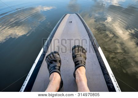 man feet in five finger water shoes on a stand up paddleboard