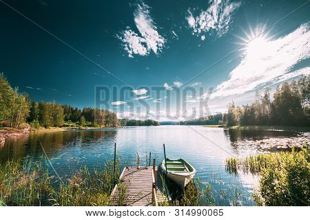 Old Wooden Fishing Boat Moored Near Pier In Summer Lake Or River. Beautiful Summer Sunny Day Or Even
