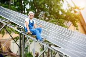 Young smiling electrician sitting on almost finished stand-alone solar photo voltaic panel system with screwdriver, showing thumb up gesture on bright sunny green tree background poster