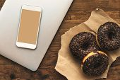 Smart phone mock up and chocolate doughnuts on table, top view of sweet sugary snack next to modern technology equipment poster