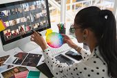 High angle view of pretty mixed-race female graphic designer working on computer and holding colour swatch at desk in office. Modern casual creative business concept poster
