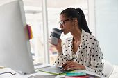 Front view of beautiful mixed-race female graphic designer having coffee while using graphic tablet at desk in office. Modern casual creative business concept poster
