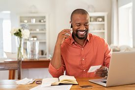 Smiling african man using laptop at home while checking home finance. Happy mature man looking at invoice while talking on phone with bank. Man checking receipt and bill while talking at phone.