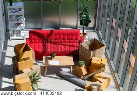 Cardboard Boxes Stacked, Plants, Comfortable Couch Near Big Window Inside Of Modern Living Room In N