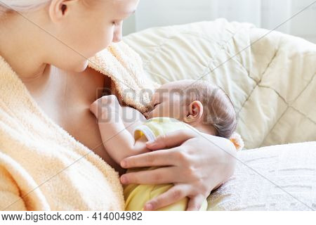 Baby Eating Breast Milk. Caucasian Blonde Young Mother Breastfeeding Her Baby Horizontal Photo. Conc