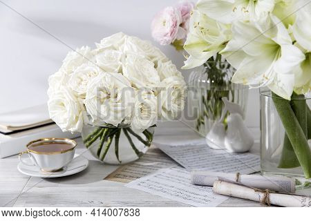 London, Uk -20 March 2021, A Bouquet Of White Roses In A Round Glass Vase On A Table With A Cup Of T