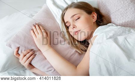 Teenager Girl In Pajamas Sleeps In Bedroom At Morning Time. Young Woman Sleeping In Bed. Portrait Of