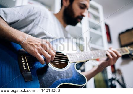 Caucasian Man With Beard Playing Acoustic Guitar In His Home Studio.focus Selective.enjoying Music