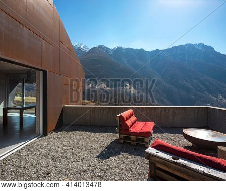 Modern house exteriors with veranda. Red sofa overlooking the mountains of Switzerland. Concept, nobody inside