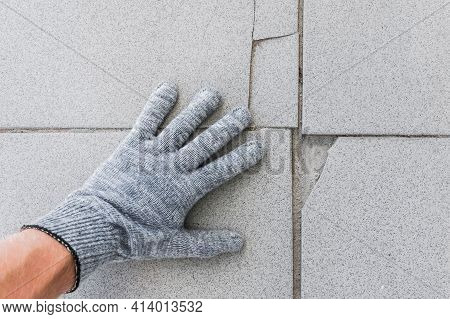 Hand Of Construction Worker In Protective Gloves Examines Old Broken Tile Floor Background. Renovati
