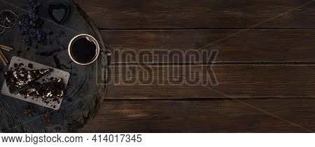 A Cup Of Black Coffee With Pieces Of Chocolate Cake On A Wooden Cracked Oak Cut, Slices Of Lemon, Gr