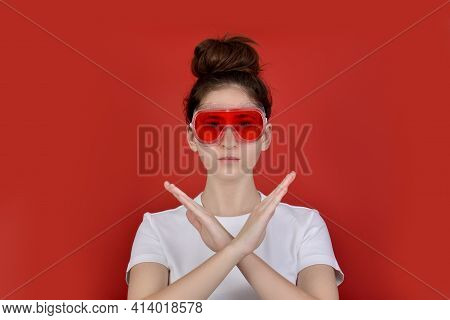 Portrait Of A Serious Young Brunette Girl In A White T Shirt And Red Safety Glasses, Gesturing No Si