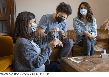 Pregnant Woman Sitting At A Home Living Room With A Group Of People, Checking The Mucus Sample Of A