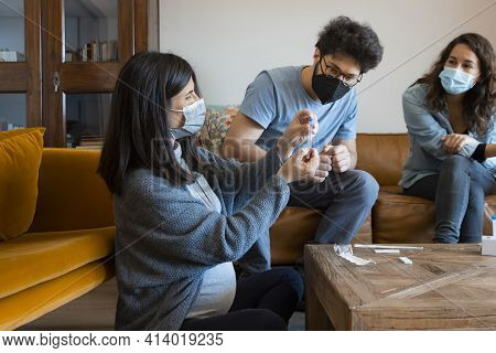 Pregnant Woman Sitting At A Living Room Of A House With A Group Of People, Introducing A Nasal Swab