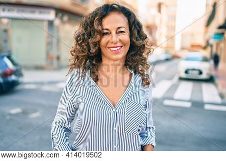 Middle age hispanic woman smiling happy walking at the city.
