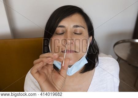 Portrait Of Relaxed Young Woman Taking A Self-swabbing Home Tests For Covid-19 At Home With Antigen
