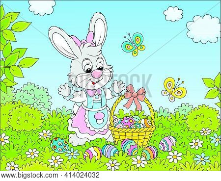 Happy Easter Bunny With A Decorated Basket Of Colorfully Painted Eggs Among Flowers And Merry Flitte